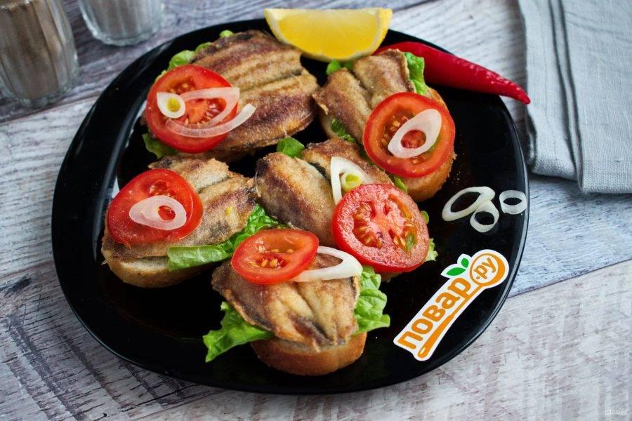 На ломтик белого хлеба положите лист салата, жаренную хамсу, ломтик помидора, кольцо лука. По вкусу полейте лимонным соком.