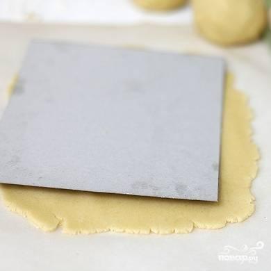 Разделяем тесто на 4 равных части, каждую из которых раскатываем так, чтобы из нее можно было вырезать квадратный пласт размером 18 на 18 см. Вырезать удобно по картонному шаблону. Каждый корж по отдельности отправляем в морозилку на 15 минут.
