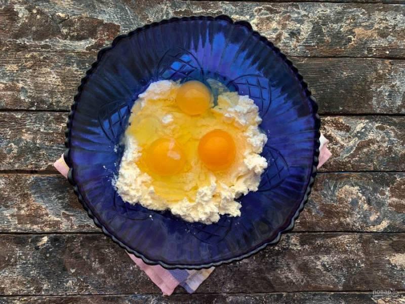 Творог разотрите вилкой, вбейте яйца и хорошо перемешайте.