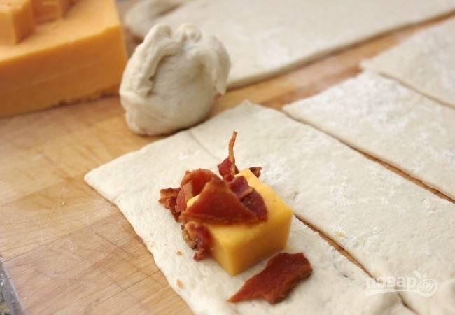 1.Готовое слоеное тесто разрежьте небольшими полосками. Полоски бекона обжарьте на раскаленной сковороде до золотистой корочки. Переложите его на салфетки и раскрошите крупными кусочками. Сыр нарежьте кубиками. Выложите на каждую полоску теста кусочек сыра, добавьте бекон.