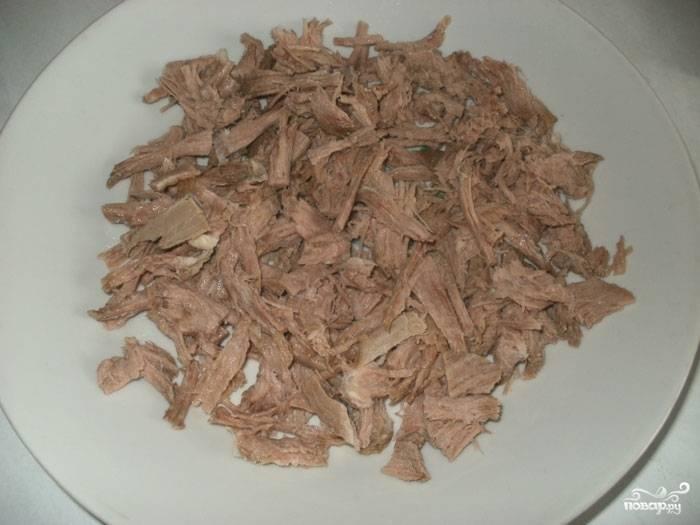 Остывшую говядину разбираем на волокна или режем небольшими кусочками. Я предпочитаю разбирать на волокна. Измельчённое мясо добавляем в бульон с овощами.