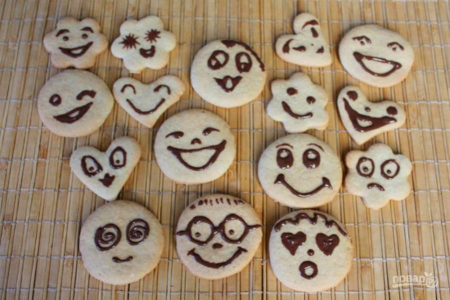 На готовое печенье наносим рисунки в виде смайликов.