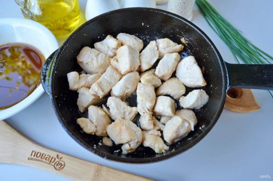 На двух столовых ложках масла обжарьте на большом огне кусочки куриного филе до золотистого цвета.