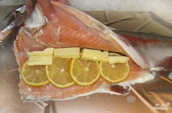 Теперь подготовьте тушку форели. Выпотрошите её, отрежьте плавники и хорошо вымойте. Затем просушите её. Смажьте сметаной с внешней стороны, а внутрь положите кусочки масла и кружочки лимона. Посолите и поперчите по вкусу.