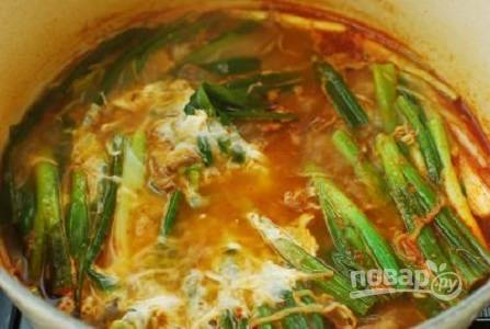 8. Добавьте бобовые ростки и варите еще минут 7. Взбейте яйца вилкой, тонкой струйкой влейте их в кастрюлю. Выложите туда же зеленый лук. Через минуту суп можно снимать с огня и подавать к столу.