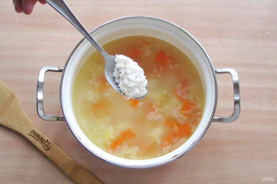Через 15 минут приготовления супа, добавьте в кастрюлю предварительно промытый рис и продолжайте варить.