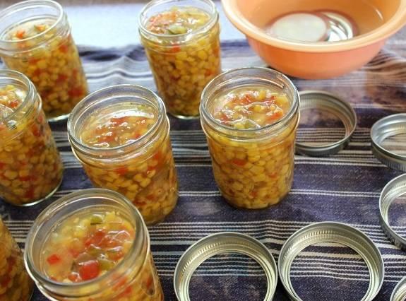 3. Понизьте огонь до медленного и варите в течение одного часа. Пока салат из кукурузы варится, стерилизуйте баночки и крышки. Затем разложите горячий салат с жидкостью по баночкам.