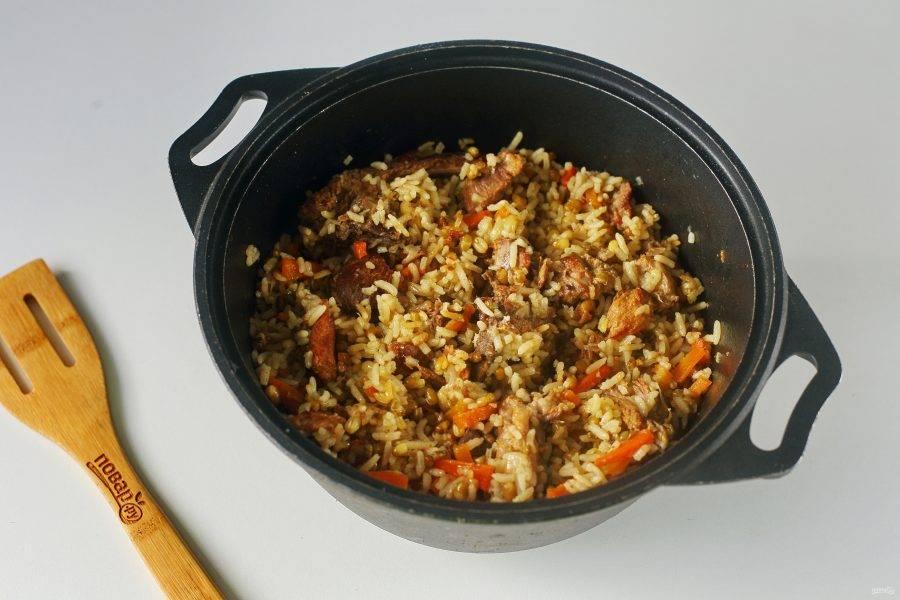 Готовьте на сильном огне до полуготовности риса, затем соберите все к центру, накройте тарелкой, затем обратно прикройте крышку и тушите еще 10-15 минут (до полной готовности). Плов с машем готов.