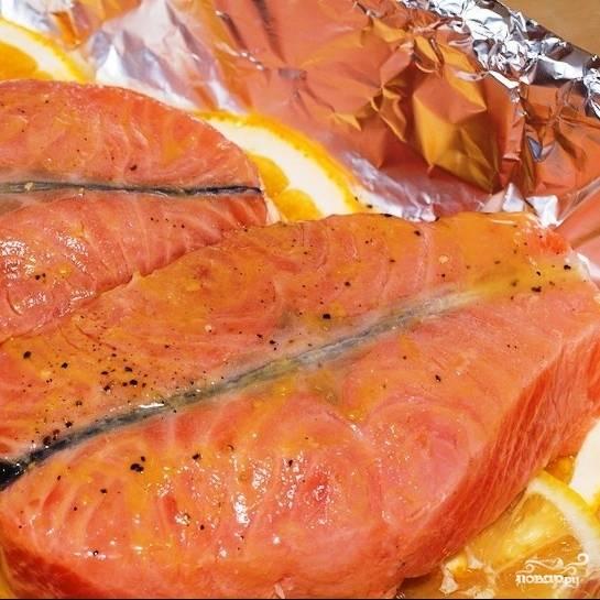 Когда рыба замаринуется, выкладываем ее на дольки цитрусовых, сверху поливаем оставшимся маринадом. Духовку ставим разогреваться до 180 градусов.