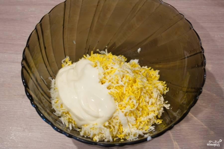 Приготовьте сырную пасту. Для этого натрите на терке плавленый сыр. Отварите 3 куриных яйца до готовности. Натрите яйца на крупной терке или нарежьте ножом на кубики. Смешайте сыр с яйцами. Добавьте немного соли и перчика. Можно добавить немного сметаны, чтобы масса была более эластичной.