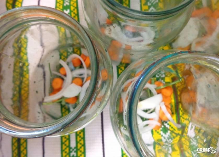 1. Огурцы моем и заливаем холодной водой. Пусть стоят три часа. Тем временем стерилизуем банки, выкладываем в них кусочки морковки и лука, а также лавровый лист, перец и укроп (по вкусу).