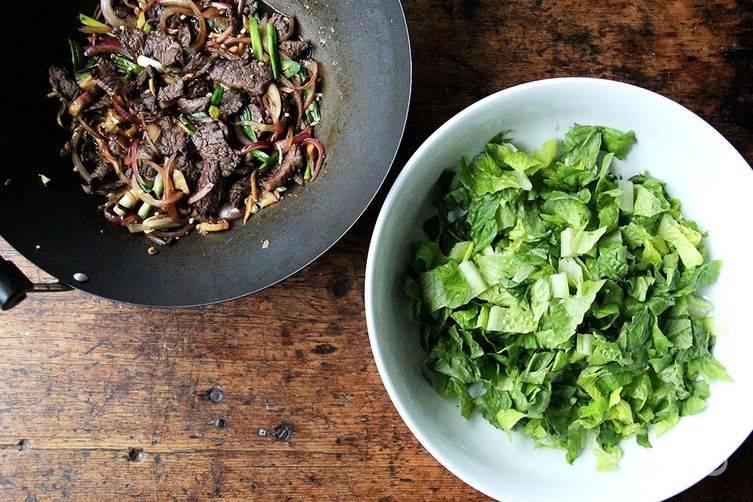 Когда мясо будет почти готово, отправьте к нему грибы и прожарьте минуты 2, затем выложите остальные овощи и припустите их буквально минуту-другую, чтобы они стали чуть мягкими. Салат нарвите кусочками.