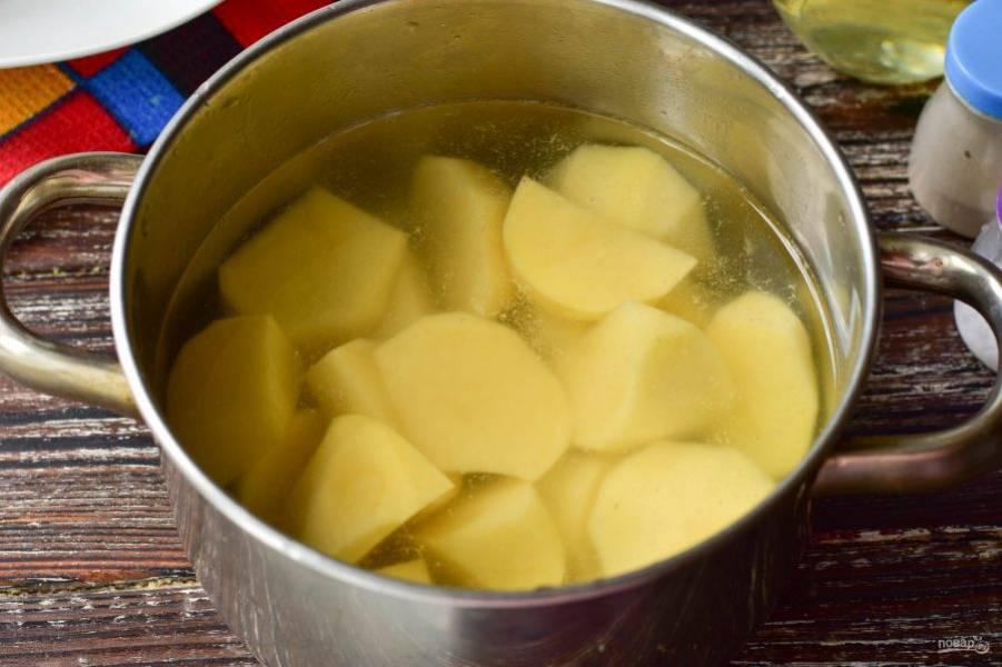 Разрежьте очищенный картофель на более мелкие кусочки. Выложите их в кастрюлю, залейте чистой водой.