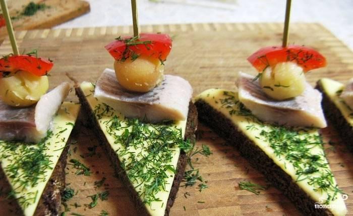 На шпажку надеваем малюсенькую отваренную картофелину и небольшой кусочек болгарского перца. Этой же шпажкой закрепляем бутерброд.
