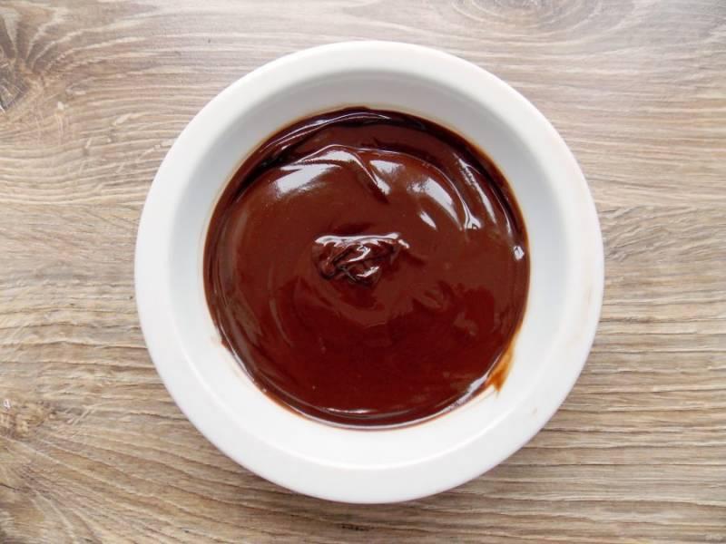 В миску поломайте оставшийся шоколад и добавьте оставшееся масло. Растопите и перемешайте до однородного состояния. Не перегрейте, иначе шоколадная глазурь расслоится.