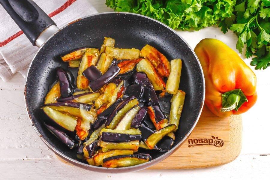 Прогрейте в сковороде с высокими бортиками растительное масло и выложите в него баклажанную нарезку. Обжарьте примерно 3-5 минут до румяности со всех сторон.