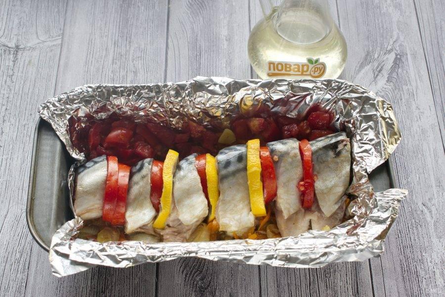 Рыбу разрежьте на куски по 2,5-3 см. Выложите в форму для запекания, чередуя с кружками томатов и лимона.