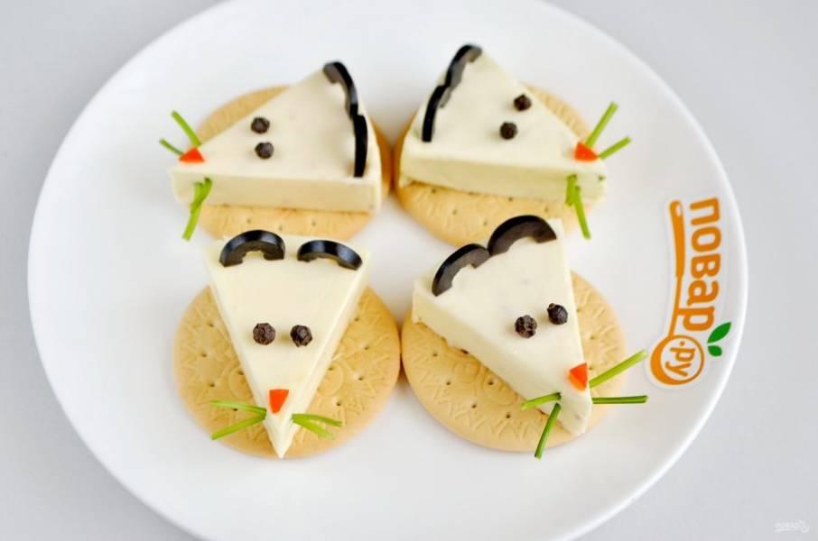 3. Оливки порежьте колечками не слишком тонко, чтобы они стояли на сыре, потом каждое колечко на половинки. Поставьте ушки. Из перца сделайте глазки. Из красного перца сделайте треугольнички для носиков.