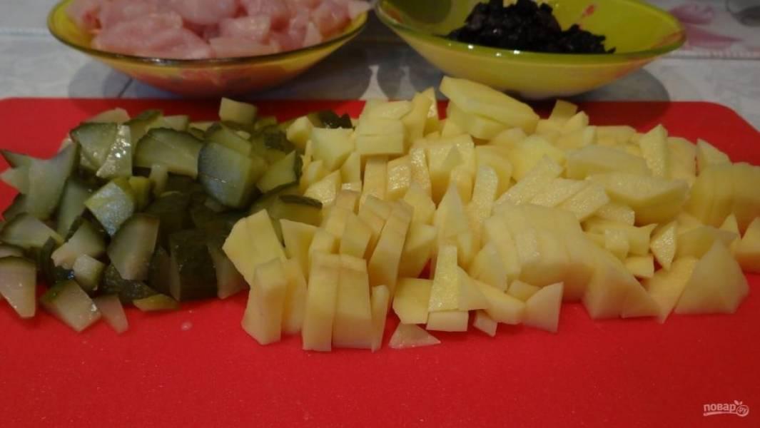Картофель почистите, промойте и нарежьте небольшими кубиками. Огурцы тоже некрупно нарежьте, а курицу нарубите кубиками в 1 см.