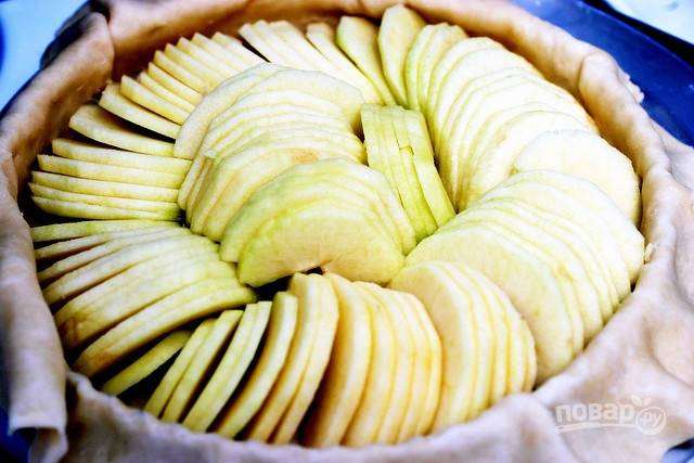В центр выложите яблоки. По краям тесто заверните внутрь.