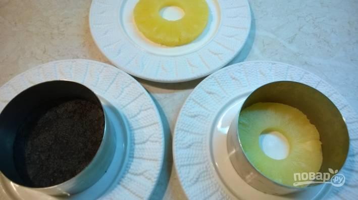 3.Подготавливаю формочку и блюдце. На дно формы выкладываю кружочек ананаса, а на него — крошку из печенья.