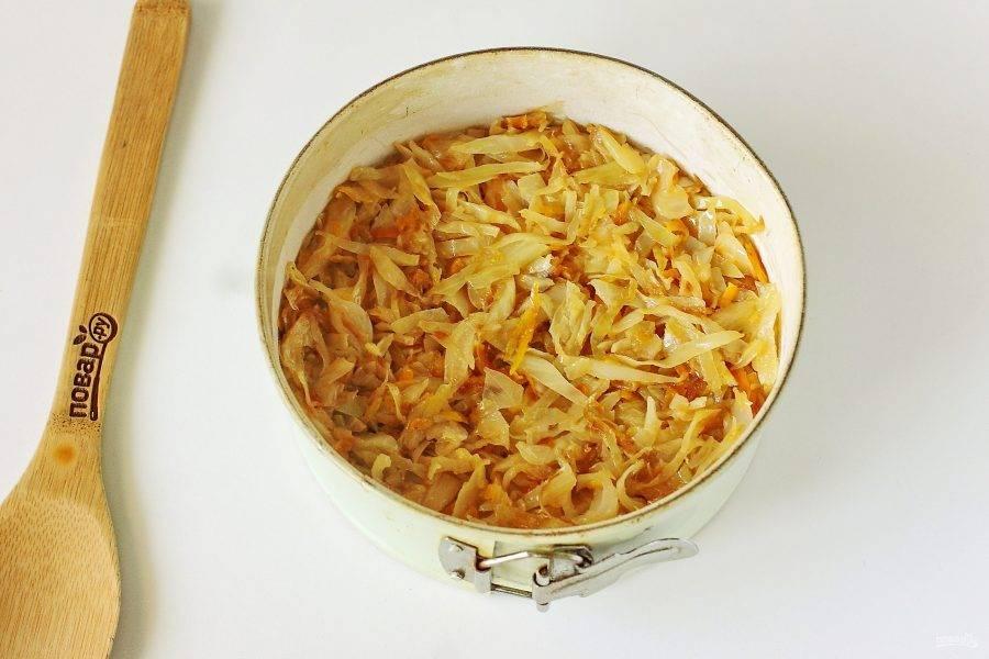 Форму для выпечки смажьте маслом. Дно и бока обсыпьте мукой или манкой. Вылейте половину порции теста и сверху равномерно распределите всю начинку. У меня тушеная капуста, но вы можете смело экспериментировать с любой другой начинкой.