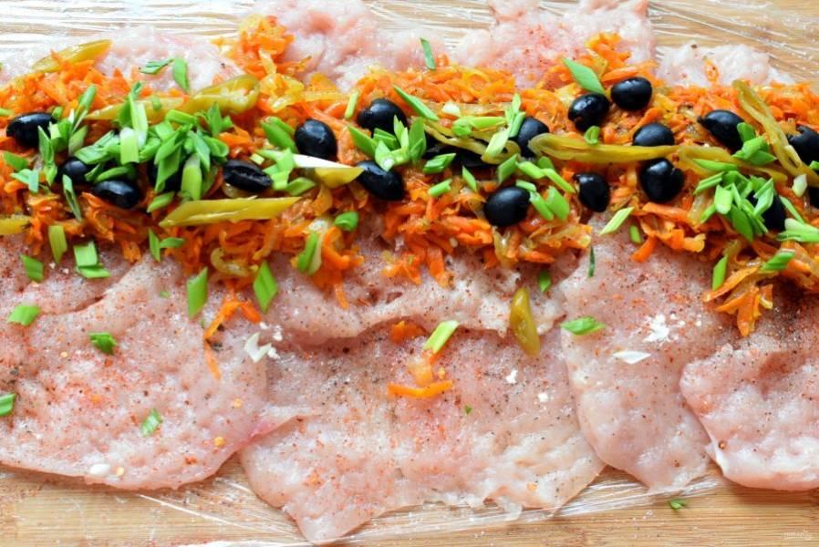 На один край выложите морковно-луковую начинку. Сверху распределите нарезанные маслины, шинкованный зеленый лук и маринованный острый перец.