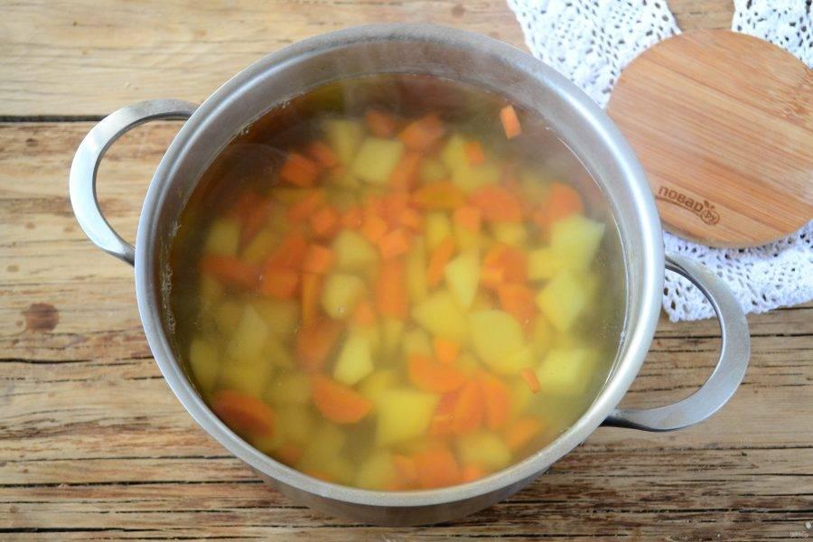 Картофель порежьте мелким кубиком и отправьте в бульон. Также мелким кубиком порежьте морковь, отправьте её к картофелю. Резать можно произвольной формой и величиной, я режу мелко просто потому, чтобы суп быстрее сварился, потом мы все равно будем его пюрировать.