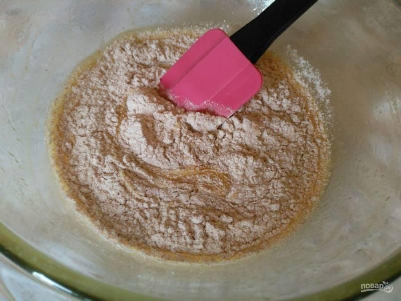 Всыпьте в яично-масляную смесь просеянную цельнозерновую муку и перемешайте с помощью ложки или лопатки.