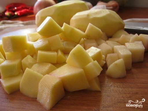 Картофель почистить, нарезать небольшими кубиками. Из бульона вытащить лавровый лист и мясо. Положить в суп подготовленный картофель.