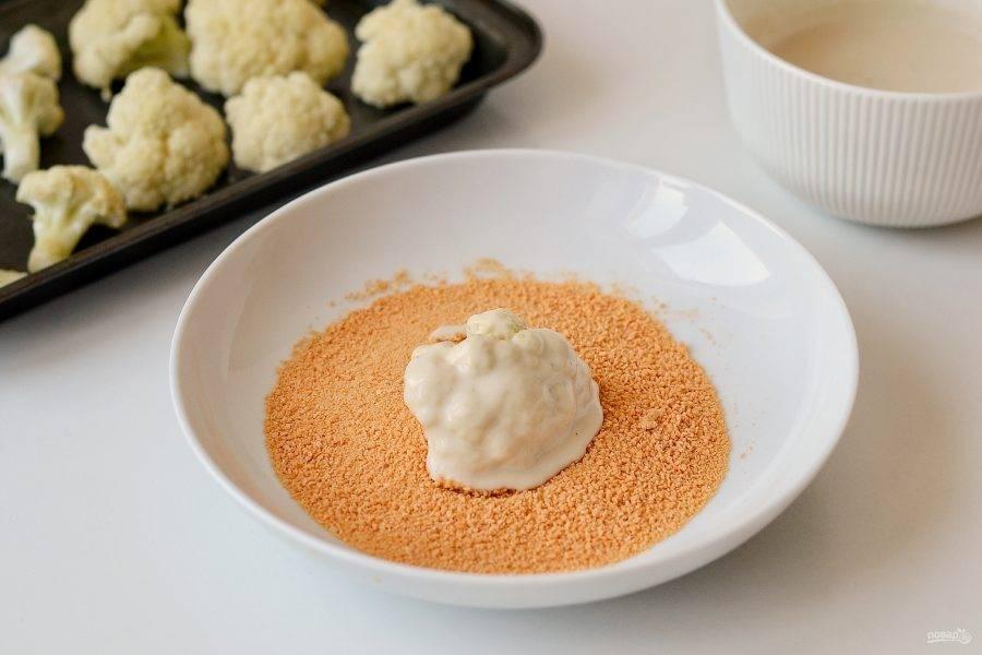 Окуните цветную капусту в кляр, затем в панированные сухари.