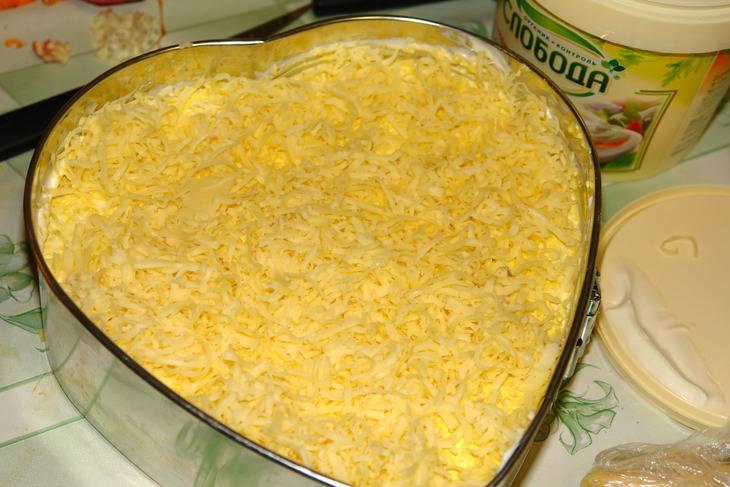 4. Далее выложить слой тертых на терке белков и немного промазать майонезом. Сыр натереть на терке и выложить в форму.