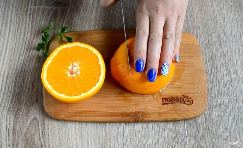 Апельсин разрежьте пополам. Половину оставьте, она понадобится для украшения блюда. А вторую половину порежьте на небольшие куски.