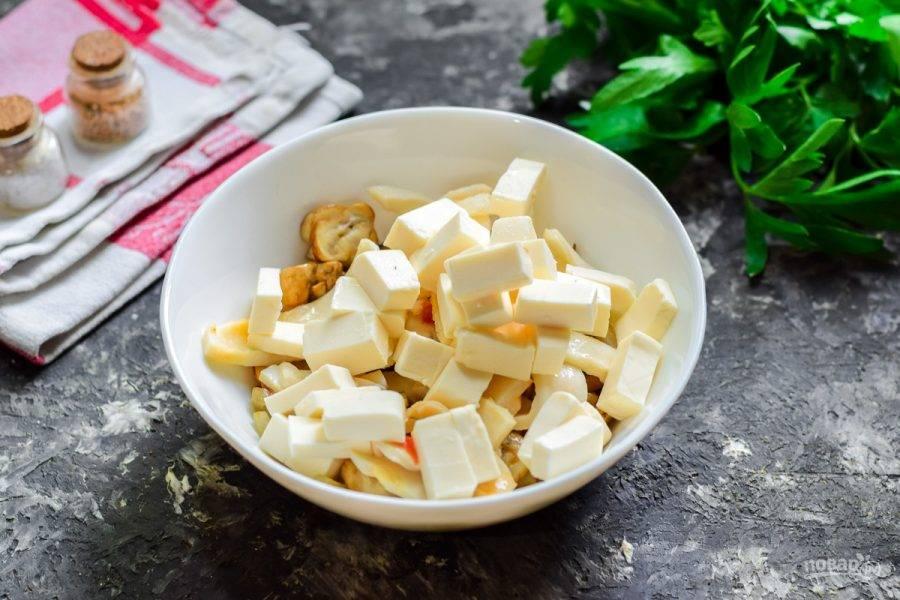 Плавленый сыр нарежьте небольшими кубиками,  переложите в салат.