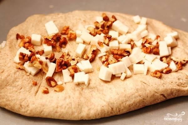 Раскатываем из нашего теста одну лепешку. Выкладываем на лепешку треть нашего сыра и орехов, вмешиваем их в тесто. Повторяем эту процедуру еще дважды.