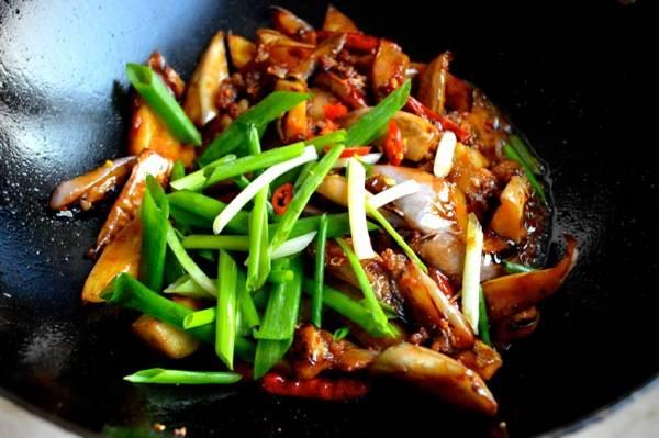 5. Выложить на сковороду баклажаны, перемешать и обжарить еще пару минут. Затем добавить перья зеленого лука.
