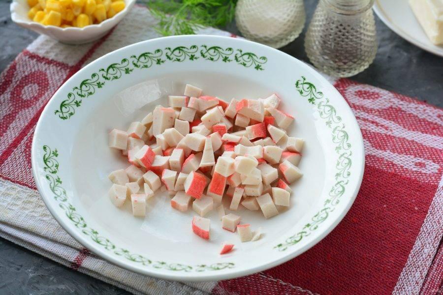 Нарежьте кубиками крабовые палочки и сложите в миску.