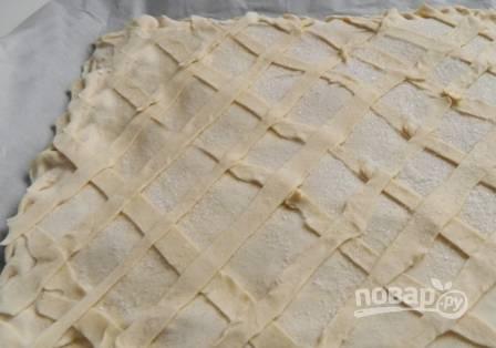 Накрываем основу пирога с начинкой вторым пластом, аккуратно защипываем края. Затем верх слегка смажем водой и украсим сеточкой из полосочек теста. Посыпаем сахаром.