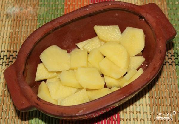 5. Картофель промойте, очистите от кожуры, разрежьте на небольшие кубики или кружочки. Выложите на дно горшочка, предварительно смазав его небольшим количеством растительного масла.