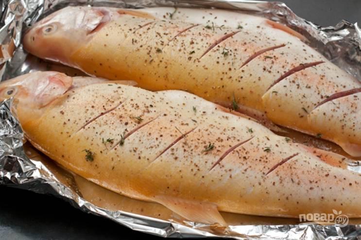 5.Застелите противень фольгой, выложите рыбку и сделайте неглубокие насечки по всей тушке, посолите и поперчите, добавьте тимьян.