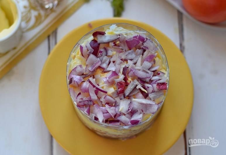 Чтобы салат имел красивую форму, можно вырезать из пластиковой бутылки круглую пустую в середине формочку. На яйца выкладываем измельченный лук.