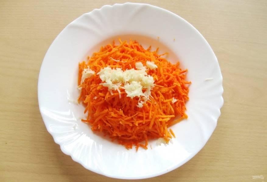 Морковь очистите, помойте. Натрите на обычной терке или на терке для корейской моркови. Чеснок очистите, измельчите любым способом. Добавьте чеснок к моркови и перемешайте.