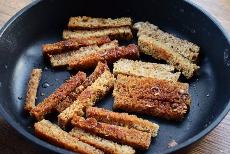 На сковороде нагрейте оливковое масло. Добавьте измельченный чеснок и брусочки хлеба. Обжарьте до румяной корочки.