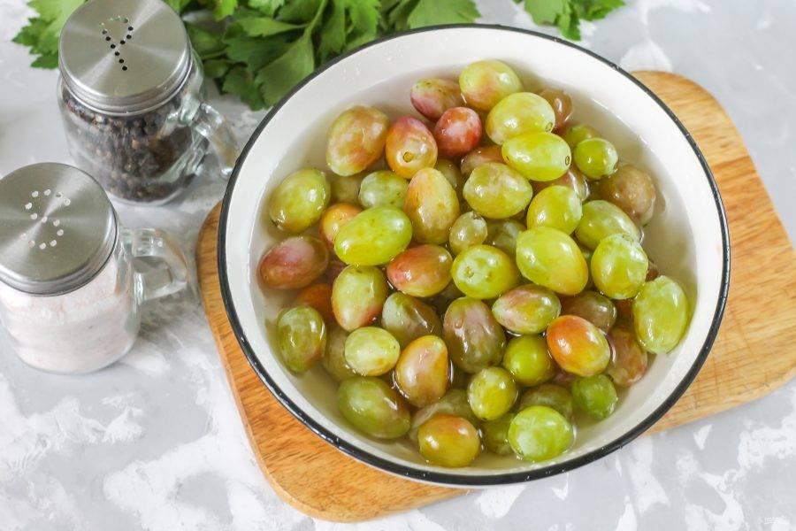 Оборвите ягоды винограда с кистей, высыпьте в глубокую емкость и промойте в воде. Лучше всего использовать спелый виноград сладких сортов. Если же ягоды кисловатые на вкус, то дополнительно всыпьте в маринад немного сахарного песка - 1-1,5 ч.л.