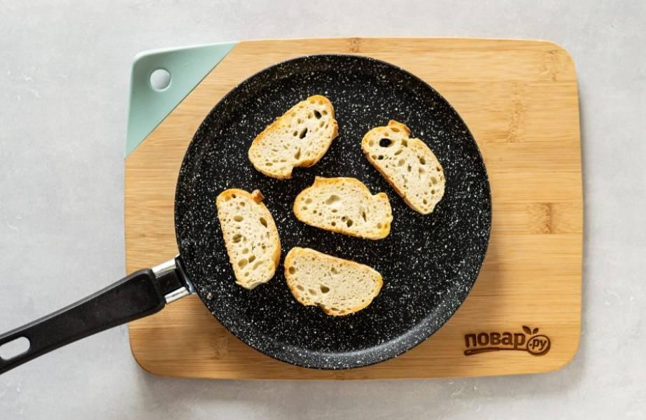 Обжарьте в сухой сковороде ломтики хлеба до хрустящей корочки.