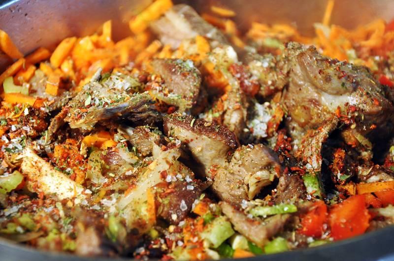 11. К поджаренному мясу отправить овощи. Добавить в сотейник приправы и, накрыв крышкой, продолжать тушить.