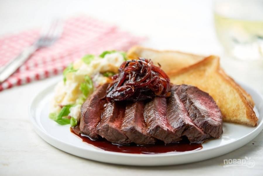 6. Подавайте стейк, нарезав его на куски, сверху выложите лук и полейте мясо соусом из-под него. Выложите на блюдо тосты и картофельное пюре с зелёным луком. Приятного аппетита!