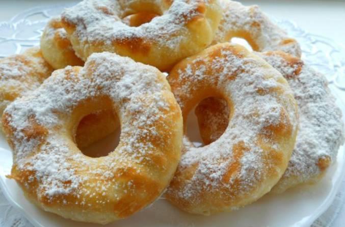 Переложите пончики на тарелку, дайте им немного остыть, посыпьте сахарной пудрой. Приятного аппетита!