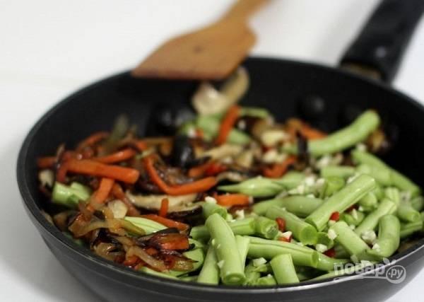 4. Выложите фасоль, добавьте по вкусу измельченный чеснок и чили перец. Помешивая, жарьте пару минут.