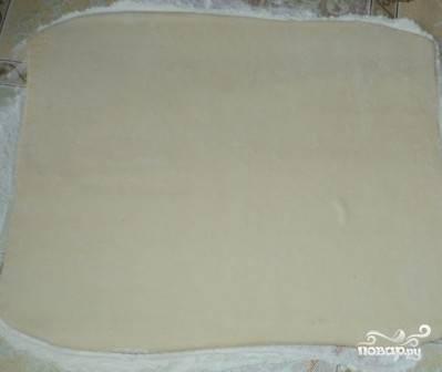 Готовое слоеное тесто делим на две части. У нас будет два пирога. Раскатываем часть теста на присыпанной мукой поверхности в пласт толщиной примерно 0,5 см.
